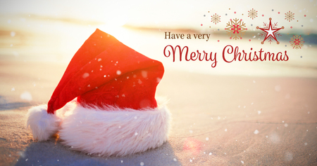 Christmas card against santa hat on the beach Stock Photo