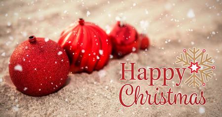 Christmas card against christmas baubles arranged on sand