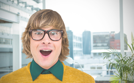 astonishing: Portrait of surprised hipster businessman  against working desk in a office