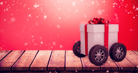 Gift box with red ribbon on wheels against multi colored christmas bauble