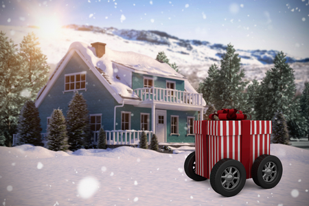 red gift box: Striped white and red gift box with wheels against snow covered house with trees Stock Photo