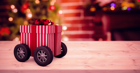 Striped white and red gift box with wheels against fake snow against christmas tree Stock Photo