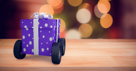 Gift box with gray ribbon on wheels  against composite image of fake snow against illuminated background Stock Photo