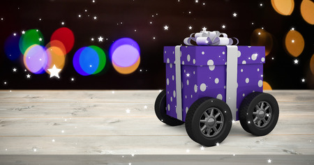 snow cone: Purple wrapped with polka dot gift box on wheels against pine cone decoration on snow
