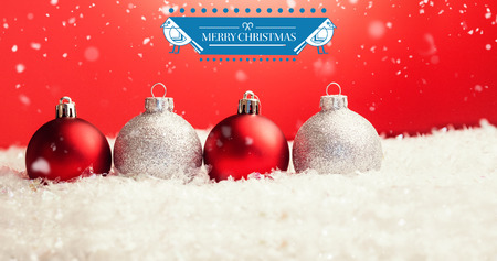 lined up: Christmas greeting  against christmas baubles on fake snow Stock Photo