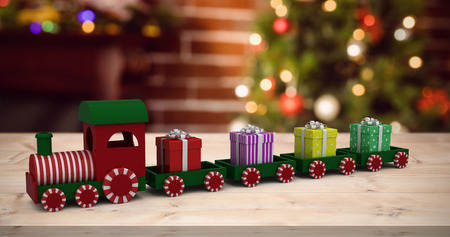 stock photo train model carrying gift boxes against fake snow against christmas tree