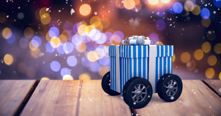 christmas gift box: Digitally generated image of gift box with wheels against defocused of christmas tree lights and fireplace