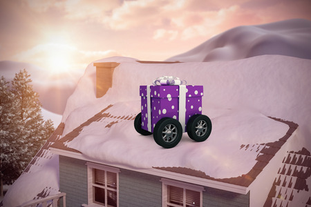 snowcapped mountain: Purple wrapped with polka dot gift box on wheels against snow covered roof of house Stock Photo