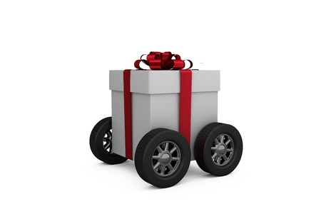 against white: Gift box with red ribbon on wheels against white background Stock Photo