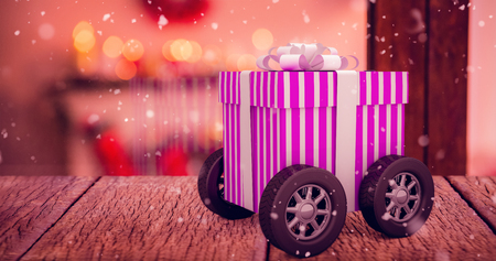 snow cone: Gift on wheels against pine cone decoration on fake snow Stock Photo