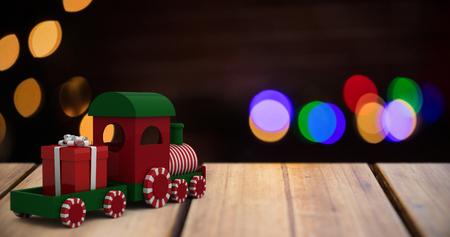 Miniature train against pine cone decoration on snow