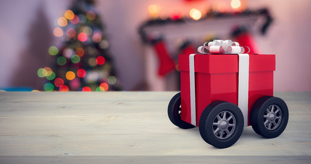 Gift box wrapped in red paper with ribbon on wheels against defocused of christmas tree lights and fireplace