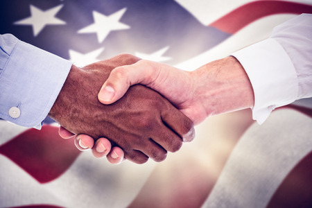 mid adult men: Close-up shot of a handshake in office against focus on usa flag Stock Photo