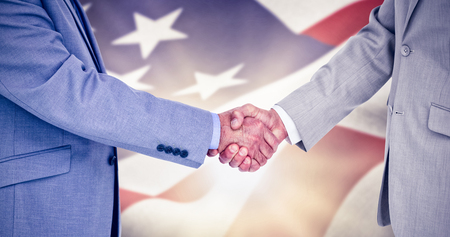 mid adult men: Side view of shaking hands against focus on usa flag