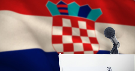 Microphone with stand on podium against digitally generated croatian national flag