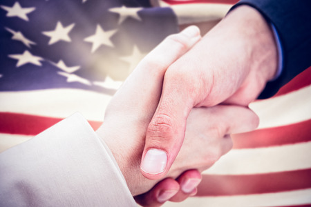 Close up on new partners shaking hands against digitally generated american flag rippling