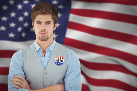 Confident businessman standing against wooden wall against political button