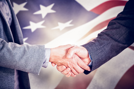 coworker: Two people having a handshake in an office against focus on usa flag Stock Photo