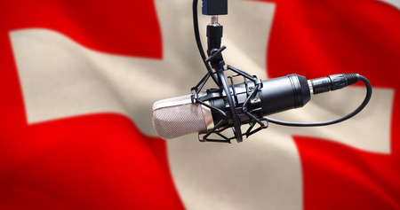 Condenser microphone against digitally generated swiss national flag Stock Photo