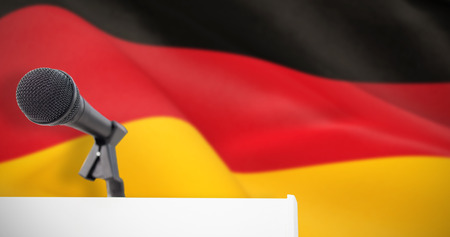 Microphone on podium against digitally generated german national flag