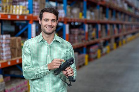 hand held computer: Portrait of worker using hand held computer in warehouse