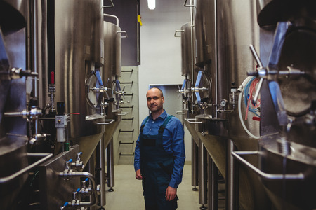 Portrait of confident manufacturer standing amidst machinery at brewery