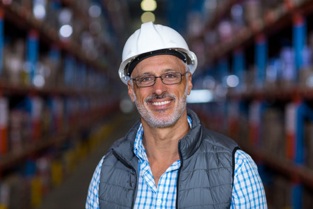 Portrait of smiling warehouse worker wearing hard hat in warehouse Stock Photo