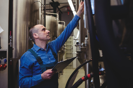 Side view of male manufacturer examining machinery at brewery Stock Photo