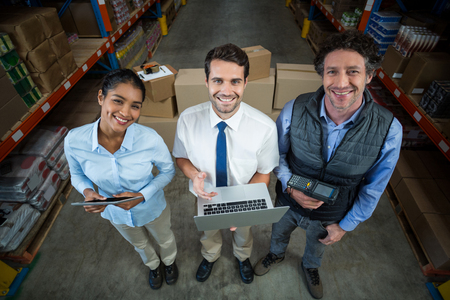 hand held computer: Portrait of warehouse manager and worker standing together in warehouse