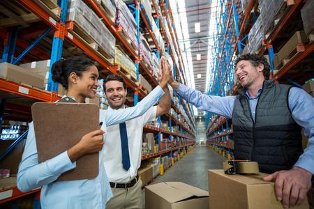 Les travailleurs d'entrepôt heureux donnant cinq haut dans l'entrepôt Banque d'images - 64457393