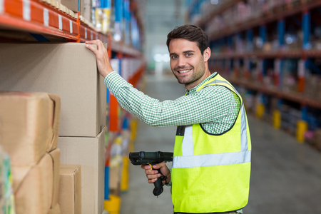 Portrait of smiling warehouse worker scanning box in warehouse Reklamní fotografie - 64457441