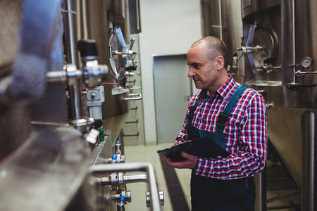 Side view of manufacturer examining machinery at brewery