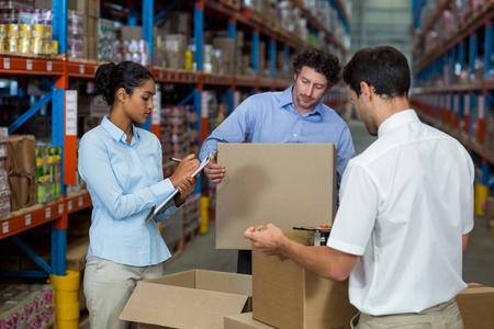 sealing tape: Warehouse workers preparing a shipment in the warehouse Stock Photo