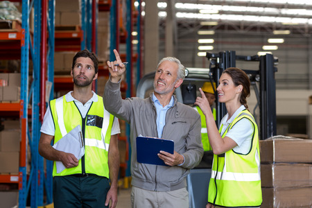 Warehouse manager and workers discussing with clipboard in warehouse Stockfoto