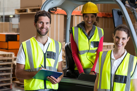 Portrait of warehouse workers and forklift driver in warehouse