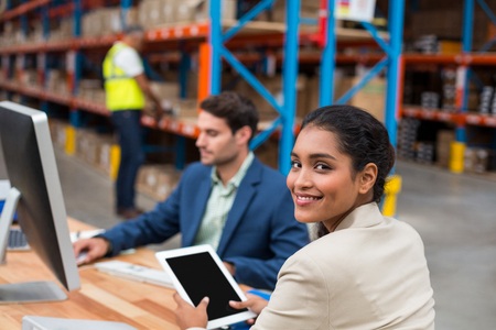 Portrait of smiling manager using digital tablet in warehouse office Imagens - 64495750