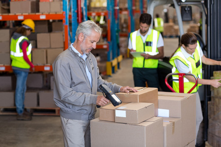 Gestionnaire d'entrepôt parcourant les boîtes dans l'entrepôt Banque d'images - 64507654