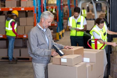 Warehouse manager scannen de dozen in het magazijn Stockfoto
