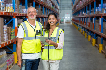 Portrait of warehouse workers standing with digital tablet in warehouse Stock Photo