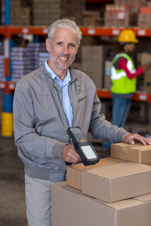 scanning: Portrait of warehouse manager scanning the boxes in warehouse