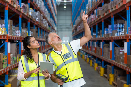 handheld device: Warehouse workers discussing with digital tablet in the warehouse Stock Photo