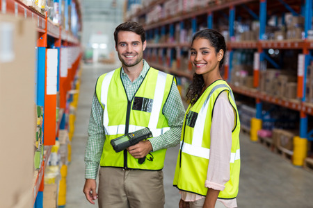 Portrait of smiling warehouse workers scanning box in warehouse