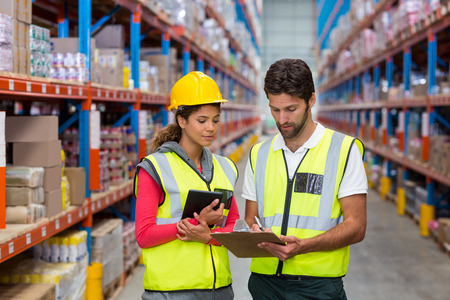 Warehouse workers discussing with clipboard while working in warehouse