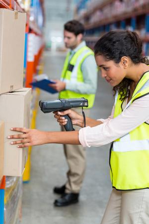 workwoman: Female warehouse worker scanning box in warehouse Stock Photo