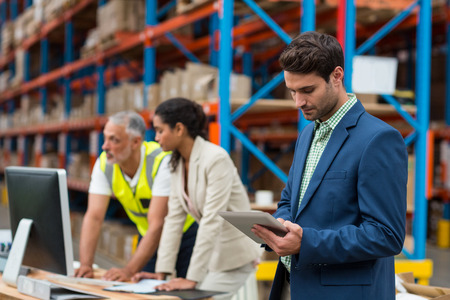 storehouse: Warehouse managers and worker working together in warehouse office