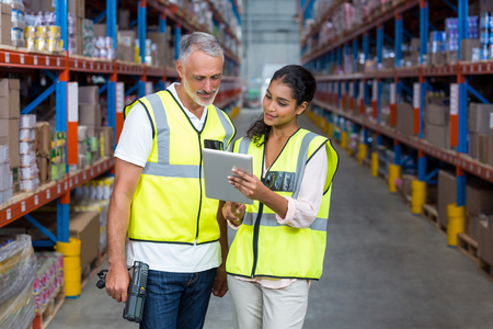 Warehouse workers discussing with digital tablet in the warehouse Stock Photo