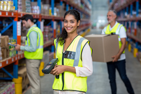 Portrait of female warehouse worker standing with barcode scanner in warehouse Stock fotó