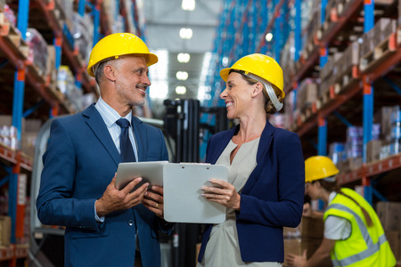 Warehouse manager and client interacting with each other in warehouse