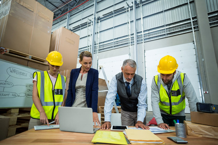 Warehouse workers and managers working together in warehouse