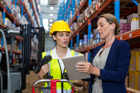 Warehouse manager with interacting female worker over digital tablet in warehouse